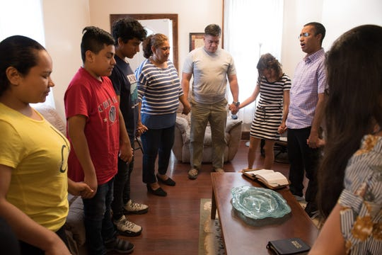 Pastor Leonid Marsan Rodriguez, right, leads a group in prayer during a Bible study at his Evansville home Saturday, July 6, 2019.