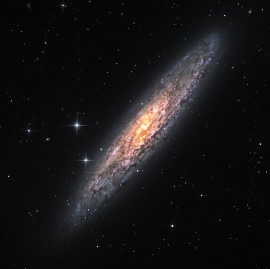 "This is NGC 253. It is a galaxy seen ""edge-on"" and lies about 11.4 million light years away. It is called a ""star burst"" galaxy because its core region is alive with star birth activity."