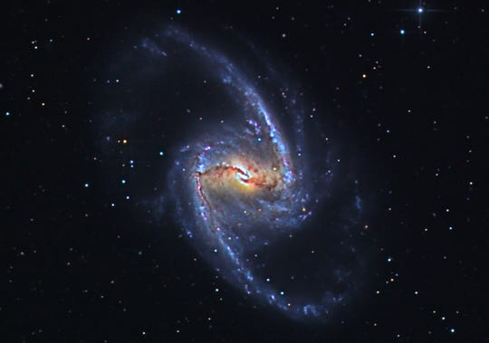 "This is NGC 1365. It's called a ""barred"" galaxy because it  has a prominent reddish colored ""bar"" running through its middle connecting the major two outer arms. It is twice as large as our own galaxy and lies 56 million light years away."
