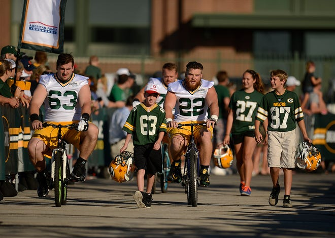 Green Bay Packers center Corey Linsley (63) and fullback Aaron Ripkowski (22) ride bikes to Packers training camp practice July 20, 2015, at Ray Nitschke Field in Green Bay.