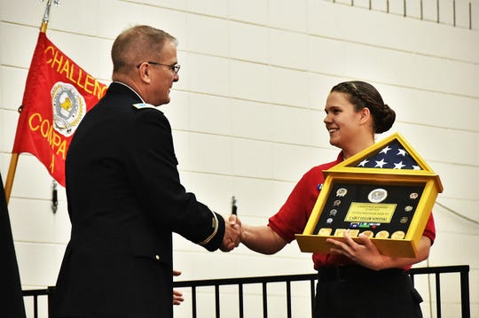 Col. Tim Covington, Wisconsin Army National Guard chief of staff, presents Wisconsin National Guard Challenge Academy Cadet Taylor Nowinski with the distinguished honor graduate award during a June 22 ceremony at Necedah High School. Challenge Academy is a voluntary program for teens at risk of not graduating high school. A military-style environment, guided by state-certified educators and counselors, develops academic skills, character, confidence and personal discipline. Class 42 had 101 cadets graduate from the 22-week residential phase of the program.