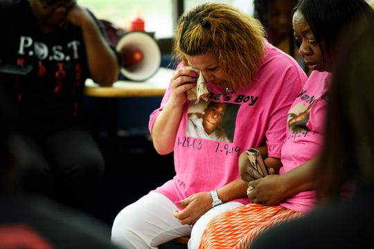 April Feaster, mother of Devon Curry, wipes tears from her eye during a candlelight vigil honoring her son's life at the Beacon Drive-In Wednesday, July 17, 2019.