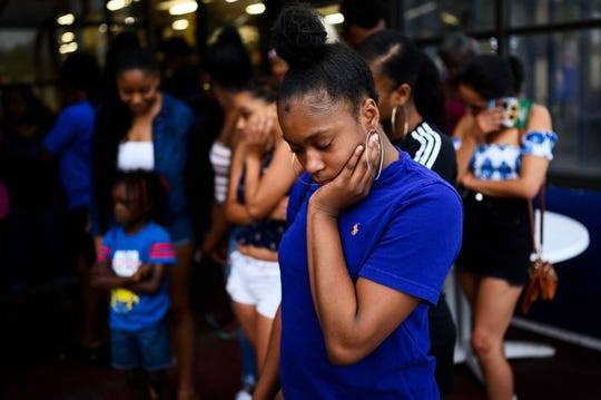 Damyah Williams, friend of 16-year-old Devon Curry, prayers during a candlelight vigil honoring Curry's life at the Beacon Drive-In Wednesday, July 17, 2019.