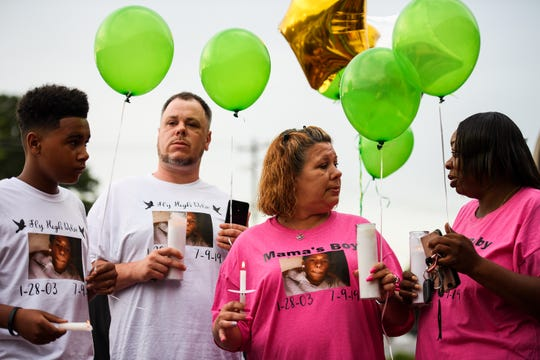 April Feaster, mother of Devon Curry, middle right, and other family members of the 16-year-old stand together during a candlelight vigil honoring Curry's life at the Beacon Drive-In Wednesday, July 17, 2019.