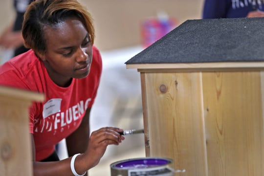 Mariah Brown and others paint Blessing Boxes as part of one of the IndyFluence projects, Thursday, July 18, 2019.  About 430 interns from several Indiana companies worked on 10 service project locations throughout Indianapolis.  The companies hope the event will convince interns to take jobs in Indiana when they enter the workforce.  The event aims to connect the workers to the community.