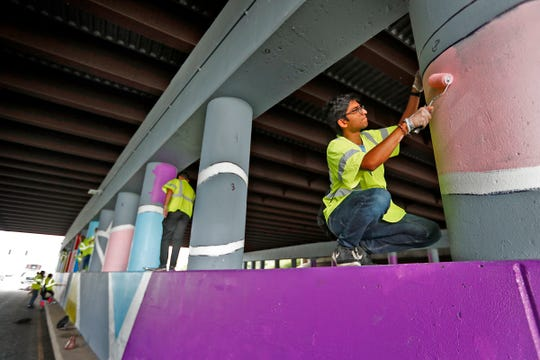 Suketu Patel, right, and others paint a mural using a paint-by-number approach at an overpass on Pendleton Pike, as part of one of the IndyFluence projects, Thursday, July 18, 2019.  About 430 interns from several Indiana companies worked on 10 service project locations throughout Indianapolis.  The companies hope the event will convince interns to take jobs in Indiana when they enter the workforce.  The event aims to connect the workers to the community.