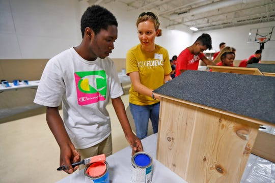 Trayshawn Hill, left, a student in the CAFE (Community Alliance Far Eastside) Summer program, and local intern Carol Yoder decide a color scheme before they paint a Blessing Box as part of one of the IndyFluence projects, Thursday, July 18, 2019.  About 430 interns from several Indiana companies worked on 10 service project locations throughout Indianapolis.  The companies hope the event will convince interns to take jobs in Indiana when they enter the workforce.  The event aims to connect the workers to the community.