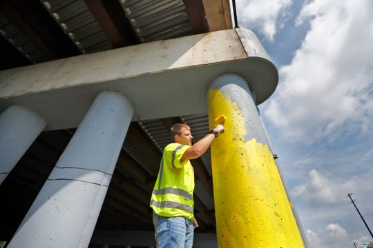 Jaret Rightley and others paint a mural using a paint-by-number approach at an overpass on Pendleton Pike, as part of one of the IndyFluence projects, Thursday, July 18, 2019.  About 430 interns from several Indiana companies worked on 10 service project locations throughout Indianapolis.  The companies hope the event will convince interns to take jobs in Indiana when they enter the workforce.  The event aims to connect the workers to the community.