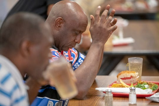 """Stan Whitley blesses his food during dinner service at Wheeler Mission shelter for men, Indianapolis, Thursday, July 18, 2019. """"Without Wheeler, there could be a lot of people dying,"""" Whitley said about the shelter that gives people on the street a place to go during inclement weather."""