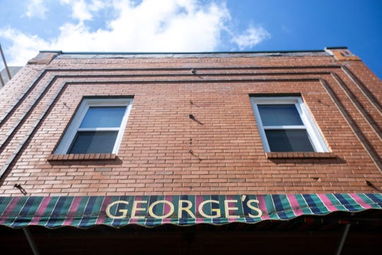 The green, blue and pink awning blows in the wind out front, Thursday, July 18, 2019, at George's Buffet along Market Street in Iowa City, Iowa.