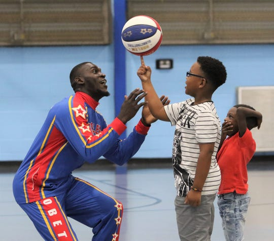 Harlem Globetrotter A.J. Merriweather, a South Side graduate, shows a child how to spin the ball on one finger Thursday at the Boys and Girls Club of Jackson.