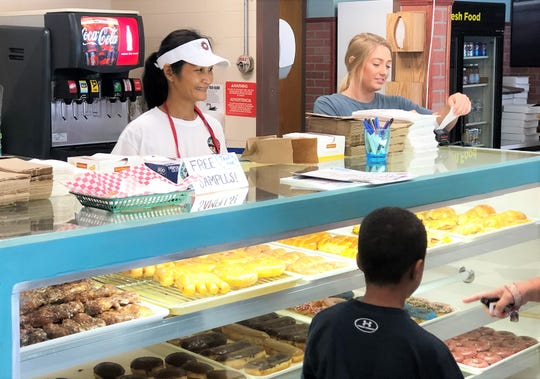 Buck'N Good Donuts owner Serah Sam Poeung and employee Madison Tidmore offer free samples and coffee while assisting customers July 16, 2019.