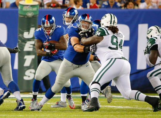 New York Giants center Jim Cordle opens hole for running back Andre Brown blocking New York Jets defensive tackle Damon Harrison in August of 2013.