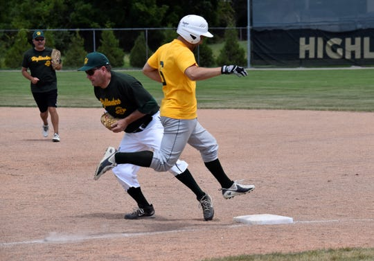 Nate Riffle, a 2010 graduate, is out at first base in a Howell alumni baseball game. Mike Brown (Class of 1979) is at first base and Phil Milner (Class of 1980) is at second.