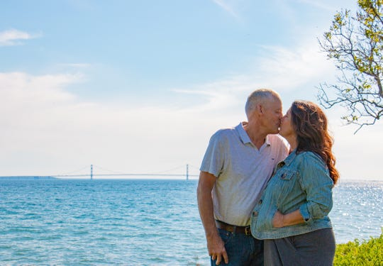 Howell natives turned Mackinac Island innkeepers Dave and Rose Witt kiss with a view of the Mackinac bridge in the background.