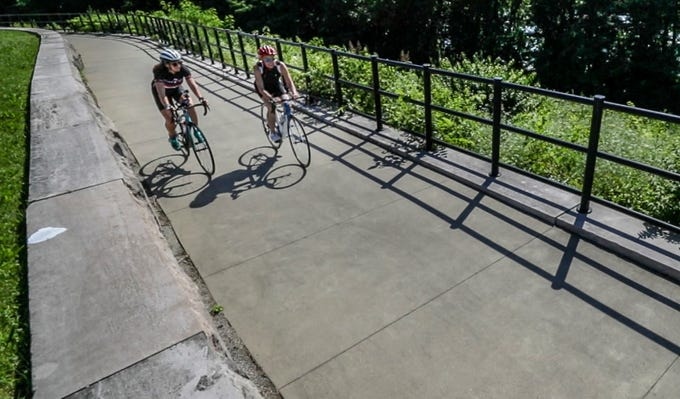 Courier Journal reporter Kirby Adams and her daughter, Jordan Grantz, ride on the Ohio River Greenway in New Albany.