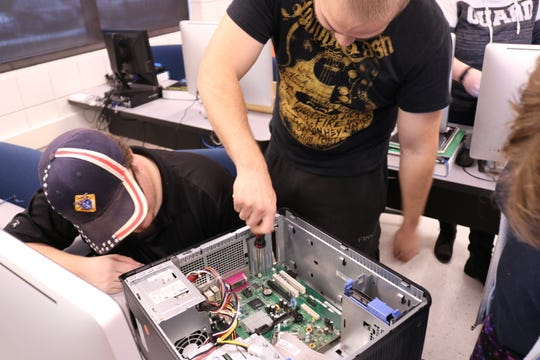 MTC students working to build a computer in class.