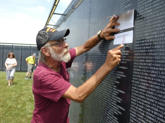 Charles Pepple, a Marine Corps veteran of the Vietnam War, makes a rubbing of one of the names on an east panel of The Wall That Heals, a traveling replica of the Vietnam Veterans Memorial in Washington D.C.
