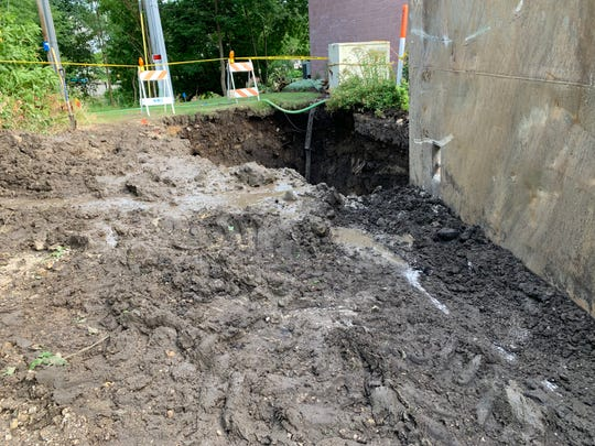 A deep muddy hole alongside The Reserve condominiums reveals the extent of the work Waukesha Water Utility crews have to conduct to fix a major water main break that occurred late on July 17.