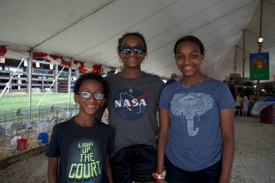 The Libbey siblings (from left) Soloman, Hannah and Rebecca enjoy the shade of the livestock tent on opening day of the 2019 Waukesha County Fair.