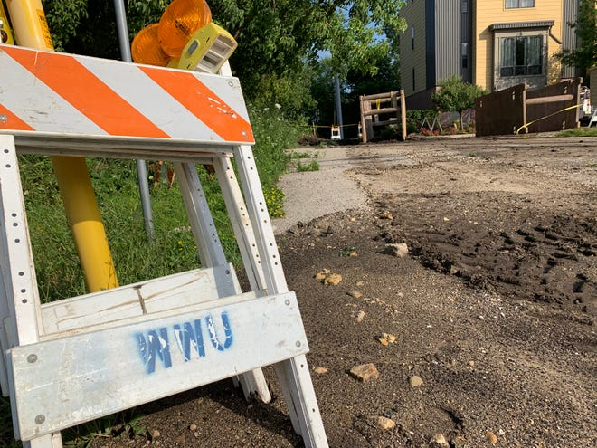 Waukesha Water Utility barricades are temporarily set aside as crews await the arrival of additional equipment to continue repairs on a significant water main break along St. Paul Avenue near Wisconsin Avenue on July 18. The break, which happened at roughly 10 p.m. the previous night, affected water pressure throughout the city.
