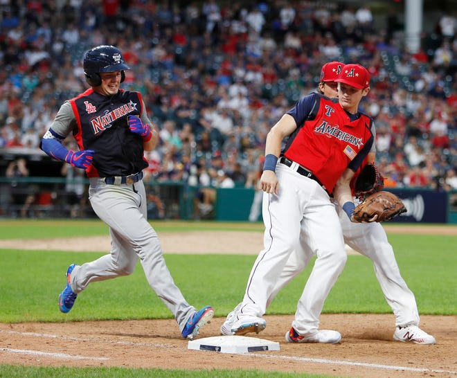 Los Angeles Dodgers prospect Gavin Lux (left) is out at first base as Minnesota Twins Jordan Balazovic (R) makes the play during the seventh inning of their SIRIUSXM All-Star Futures Game at Progressive Field in Cleveland, Ohio, on July 7, 2019.