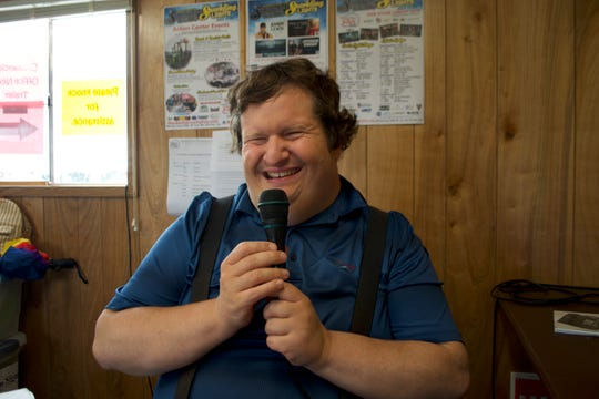 Gregg Wandsneider, the voice of the Waukesha County fair, smiles with the microphone in hand just before making an announcement July 17.