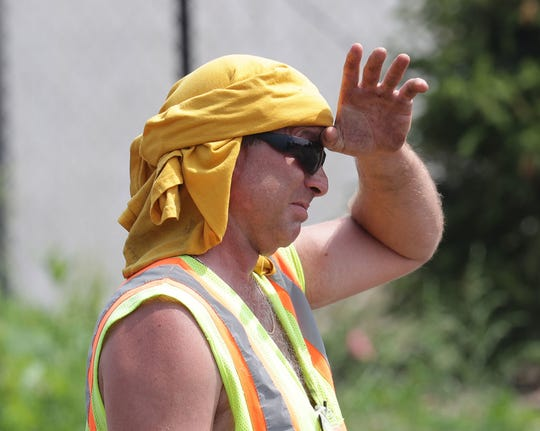 Poblocki Paving truck foreman Mike Becker uses his shirt to keep cool as he wipes sweat from his forehead while working on paving a lot at FIS, 4900 W. Brown Deer Road, in Brown Deer on Monday. The heat index -- what the temperature actually feels like when combined with humidity -- in Milwaukee briefly touched 96 degrees on Monday. The job was just one of many where employees are doing what they can to deal with the high heat and humidity  this week.
