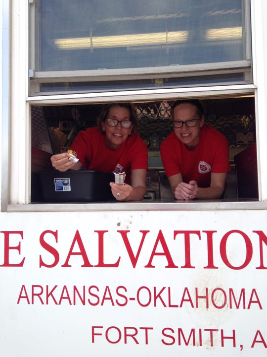 Salvation Army of Mountain Home volunteers (from left) Lisa Webb and Christy Esely had out snack bars from the service window of the organization's canteen last month in Oklahoma. The canteen, a mobile kitchen the size of a moving van, is stocked with enough supplies to feed several hundred people on demand.