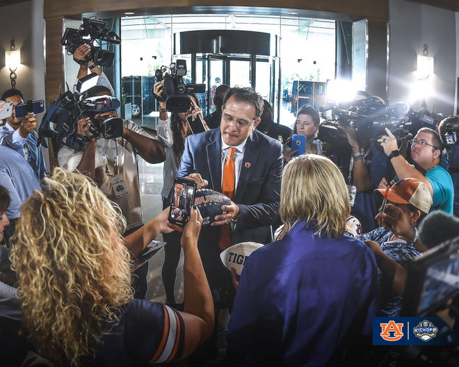 Auburn coach Gus Malzahn signs autographs at SEC Media Days on July 18, 2019, in Hoover, Ala.