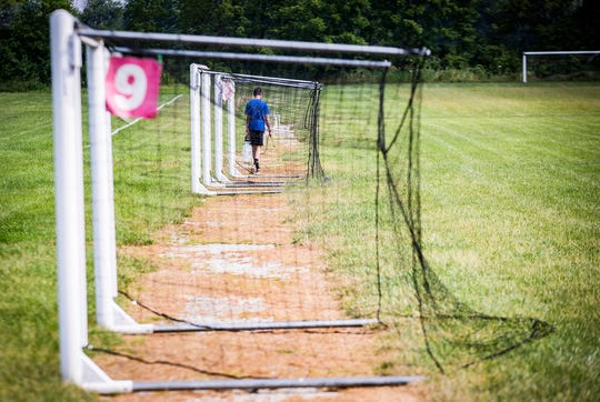 A summer employee sprays for weeds at the Yorktown Sports Park.