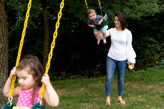 Channel 4 anchor Lauren Lowrey pushes her children, Landon and Samantha, on the swings at their home July 18, 2019.