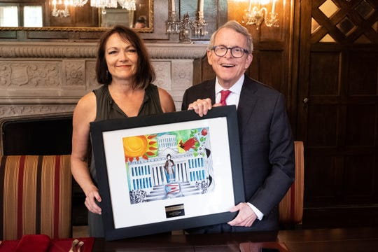 Local Artist Gayla Smith poses with Governor Mike DeWine after presenting her painting to him on July 17.