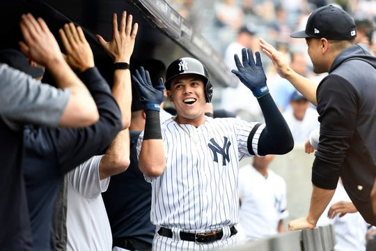 Gio Urshela #29 of the New York Yankees high-fives his teammates after hitting a home run during the second inning of game one of a doubleheader against the Tampa Bay Rays at Yankee Stadium on July 18, 2019 in New York.