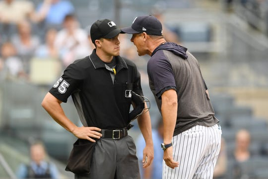 Manager Aaron Boone #17 of the New York Yankees argues with home plate umpire Brennan Miller #55 during the second inning of game one of a doubleheader after getting tossed out against the Tampa Bay Rays at Yankee Stadium on July 18, 2019 in New York.