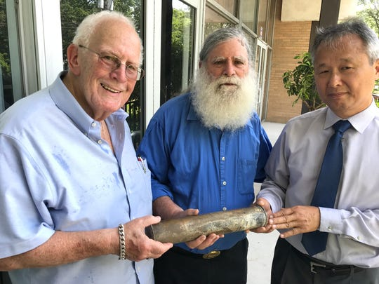 A time capsule buried under the area near the front entrance of the former New Milford Jewish Center/Congregation Beth Tikvah, now the Top Stone Church, is being held by Bob Nesoff, left, Howard Cohn, center, and David Yi, right.