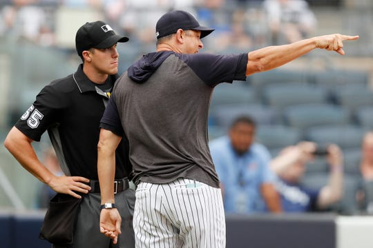 New York Yankees' Aaron Boone, right, points while yelling at home plate umpire Brennan Miller during the second inning of game one of a baseball doubleheader against the Tampa Bay Rays, Tuesday, July 16, 2019, in New York. Boone had already been ejected when he expressed his displeasure with the umpire's calls.