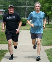 Mike Silvio, right, and his training and running partner Kirk Vickers run near the Livonia City Hall on July 18, 2019. Some heart surgery a number of years ago inspired Silvio to keep pursuing fitness goals and he's now run through every block in Livonia as he looks to take on more marathons in the future.