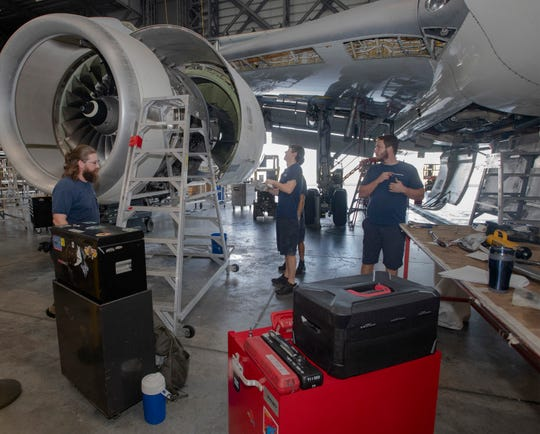 ST Engineering workers service an aircraft engine at the Pensacola International Airport on Thursday.