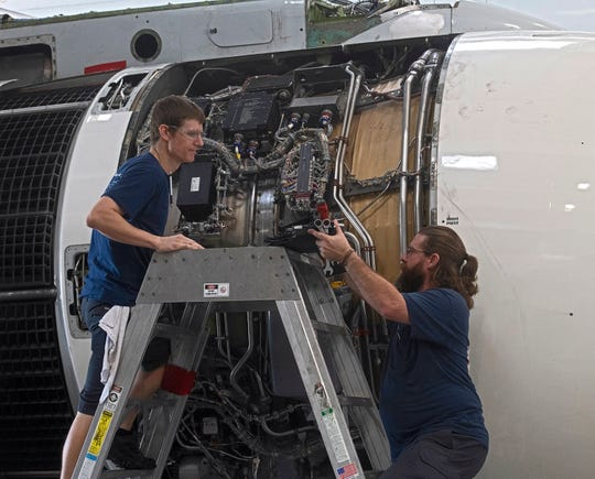 Andy White and Dylan Hoover service an aircraft engine Thursday at the ST Engineering hangar at the Pensacola International Airport.