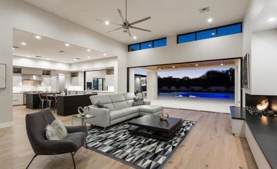 The $3.3M Paradise Valley mansion, sold by Modern Built, LLC and FKA 9148 N. 66th Place, LLC, features a great room with a fireplace and a retractable glass wall that opens to a covered patio and mountain views.