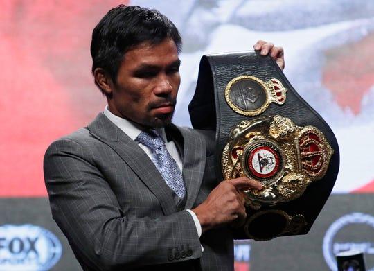 Manny Pacquiao sostiene el cinturón de campeón.
