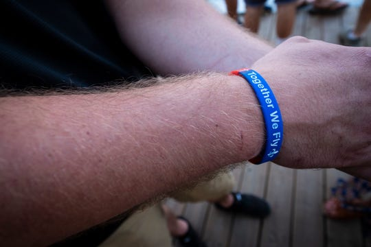 Zach Leach wears a bracelet in memory of Riley Gleason Thursday, July 18, 2019. Leach is giving out the bracelets for a donation of $5, and said he ran out within several minutes of setting up at a city event. Gleason was found dead several days after disappearing in the St. Clair River on July 12.