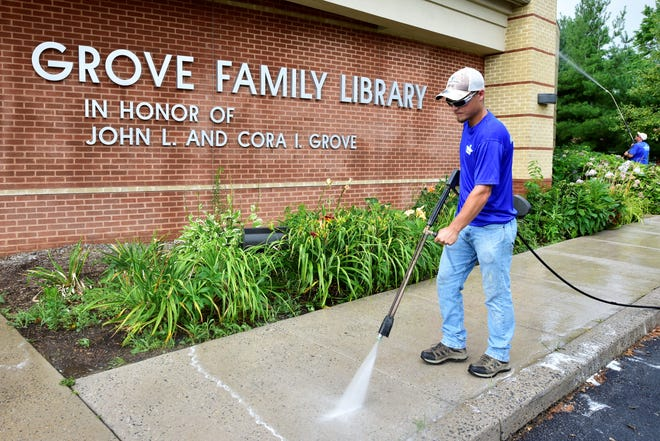 Jared Grove of Mobile Works Pressure Washing uses a pressure washer to clean the sidewalk at Grove Family Library in Chambersburg on Thursday, July 18, 2019. Mike Stitely works in the background.
