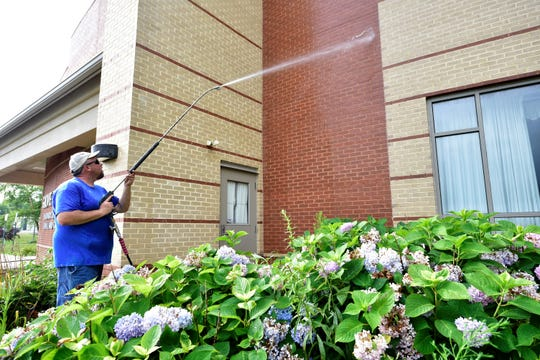 Mike Stitely pressure washes the exterior of Grove Family Library in Chambersburg on Thursday, July 18, 2019.