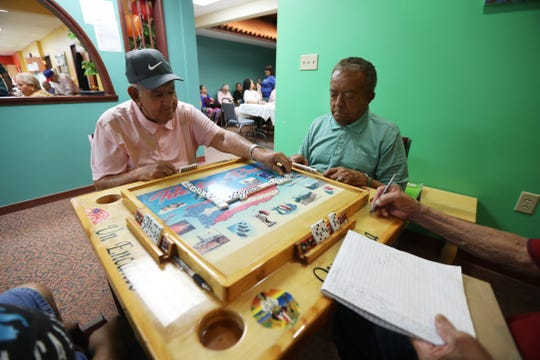 Andres Torres places his domino while Jose Diaz Diaz watches.  The two were playing with Felix Irizarry, keeping score, and Hector Lopez, just out of the frame, at Ibero-American Action League Centro de Oro on July 17, 2019.