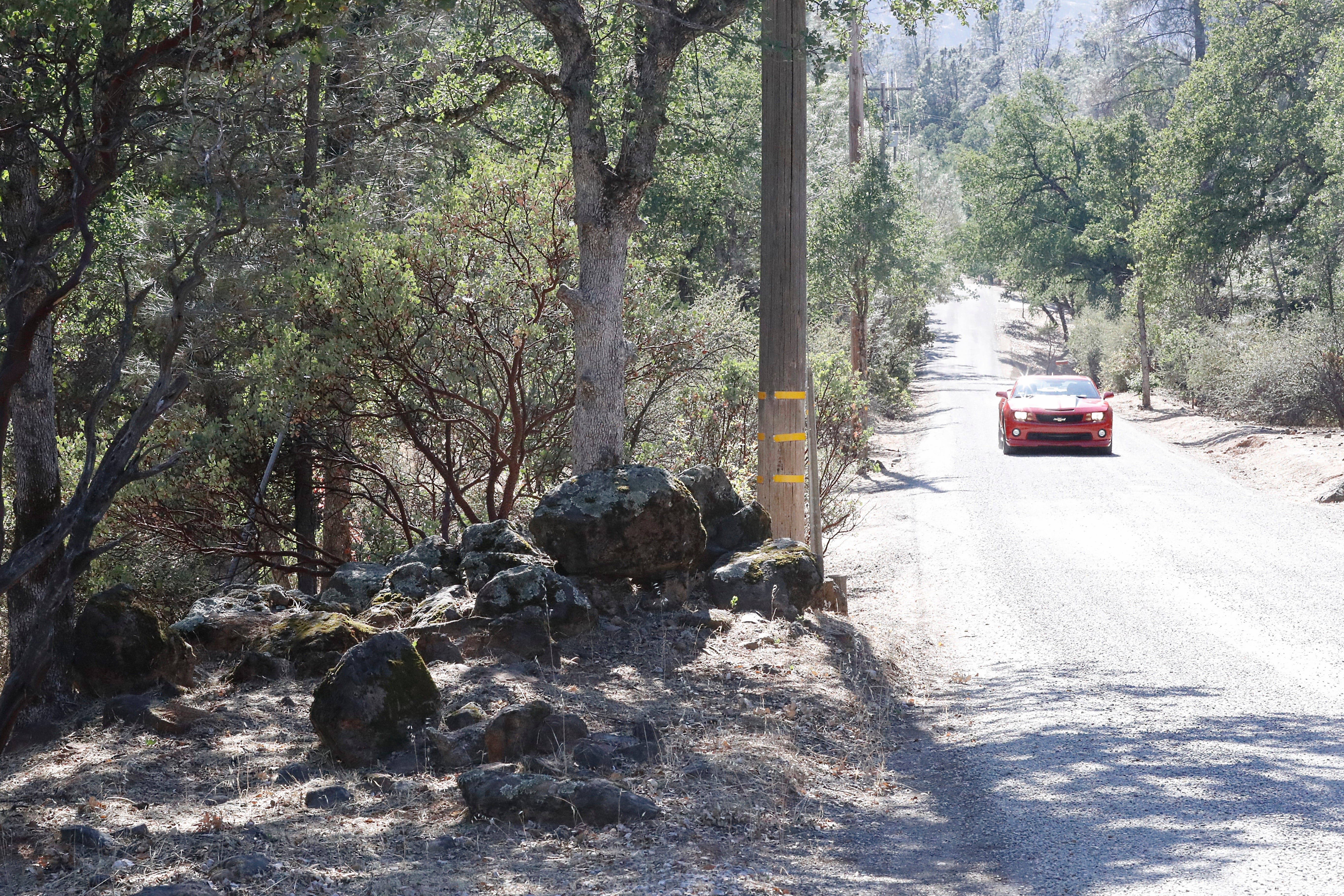 A car drives down Trail Drive where land managed by the Bureau of Land Management sits next to homes.