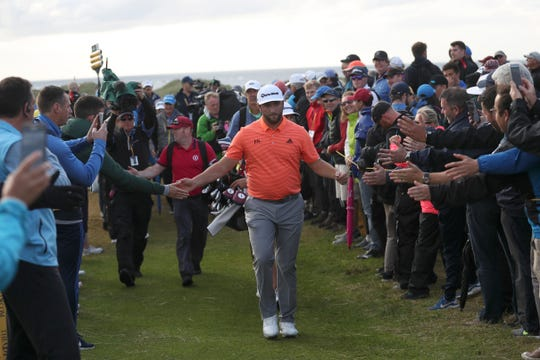 Spain's Jon Rahm reaches out and touches the hands of spectators as he walks to 17th tee during the first round of the British Open Golf Championships at Royal Portrush in Northern Ireland, Thursday, July 18, 2019.