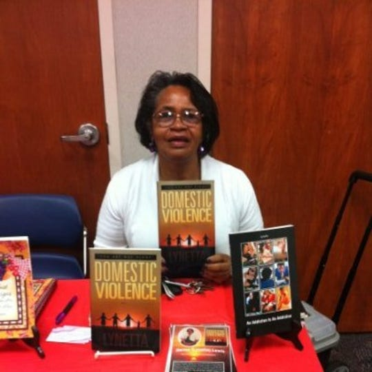 Norma Whitaker with her book about domestic violence.