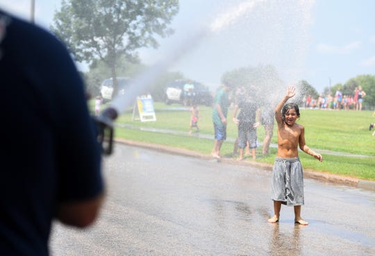 Roger Holloway, 8, is sprayed by Captain Jim Haiar with the Sioux Falls Fire Rescue during the Hydrant Block Party, in Hayward Park, Thursday, July 18. The Sioux Falls police and fire departments teamed up with the city's parks and recreation department to host Hydrant Block Parties every Thursday from 1 p.m. until 3 p.m.